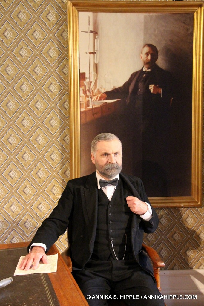 A costumed guide portraying Alfred Nobel poses with a portrait of the man himself.